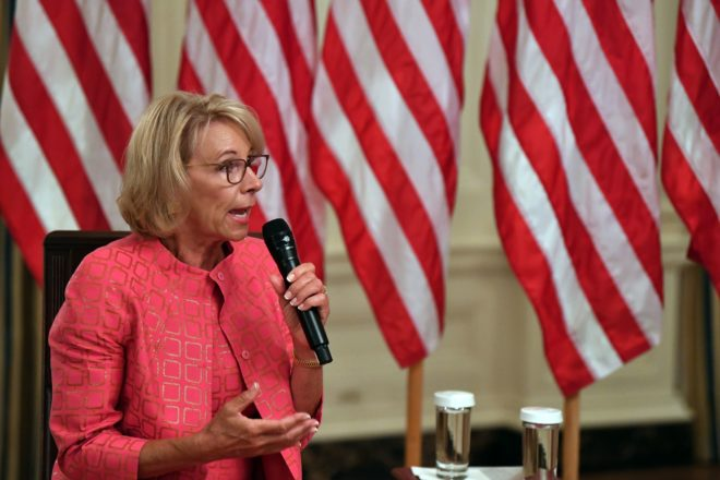 Photo of Betsy DeVos sitting in chair and speaking into a microphone